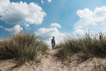 Low angle view of boy standing on sand at beach against sky during sunny day - CAVF59503