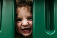 Portrait of cute playful girl making face while peeking through outdoor play equipment - CAVF59515