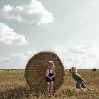 Landscape of two children playing with hay bales in a field - INGF08967