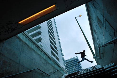 Low angle view of a man in mid air under a grey sky in Berlin - INGF09006