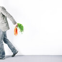 A man in casual clothing holding carrots on a white background - INGF09012