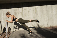 Side view of young woman exercising on metal against wall - CAVF59555