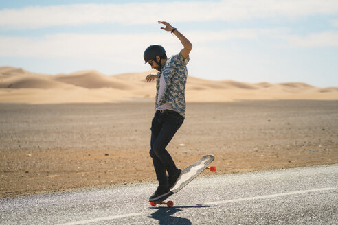 Man skateboarding on road during sunny day - CAVF59573