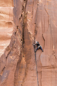 Rear view of female hiker rock climbing - CAVF59591