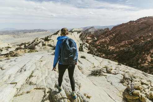 Rear view of female hiker with backpack walking on rock during sunny day - CAVF59642