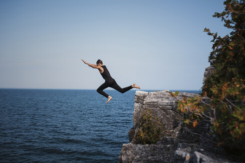 Full length of hiker cliff jumping against sea and clear sky at Bruce Peninsula National Park - CAVF59651