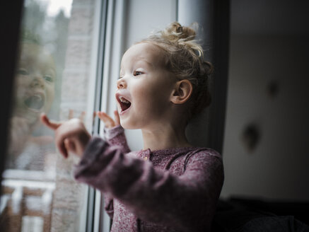 Girl with mouth open looking through window while standing at home - CAVF59654