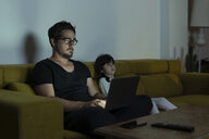 Father with daughter sitting on couch using laptop at night - ERRF00291