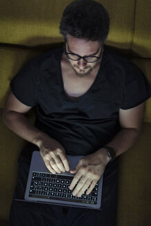 Man sitting on couch using laptop at night - ERRF00297