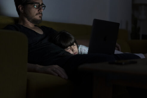 Father using laptop on couch at night with daughter sleeping - ERRF00303