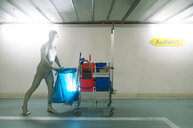 One person in a white costume pushing a cleaning trolley - INGF09216