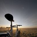 Bicycle overlooking a natural landscape in a field under clear skies in Germany - INGF09288