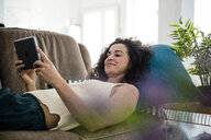 Mature woman lying on couch, using digital tablet - MOEF01903
