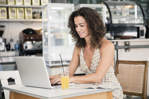Mature woman sitting in coffee shop, using laptop - MOEF01921
