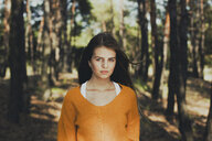 Portrait of a young woman standing in the forest - INGF09357