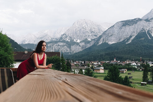 A woman sitting at a wooden table overlooking the mountains - INGF09390
