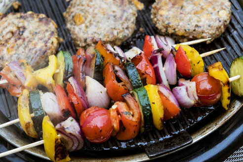 Food on a barbeque, vegetable kebabs and home made burgers, cooking outdoors. - MINF09720