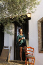Spain, Andalusia, young woman with cup uf coffee standing barefoot at house entrance looking at distance - ERRF00325