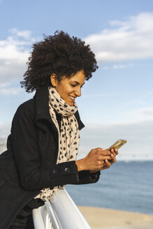 Smiling woman leaning on railing looking at cell phone - AFVF02065