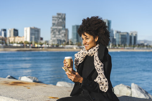 Spain, Barcelona, portrait of smiling with coffee to go and smartphone sitting on a wall - AFVF02068