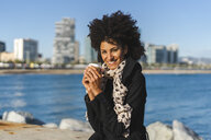 Spain, Barcelona, portrait of smiling woman with coffee to go - AFVF02071