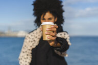 Woman's hand holding coffee to go, close-up - AFVF02074