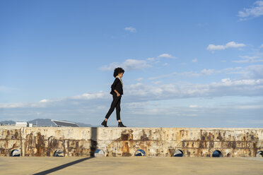 Spain, Barcelona, woman dressed in black walking on wall at sunlight - AFVF02080