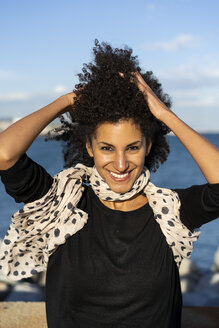 Portrait of smiling woman with blowing scarf and hands in her hair - AFVF02083