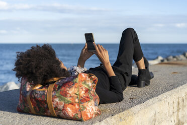 Woman dressed in black relaxing on a wall in front of the sea using smartphone - AFVF02089