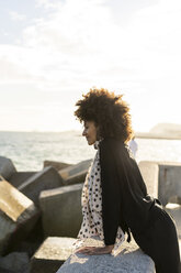 Profile of smiling woman leaning on a wall near the sea - AFVF02092