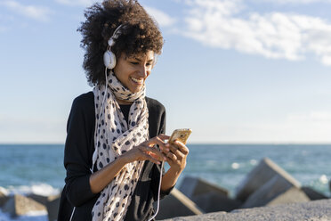 Portrait of smiling woman listening music with smartphone and headphones near the sea - AFVF02101