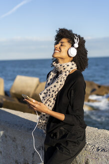Smiling woman listening music with smartphone and headphones near the sea - AFVF02104