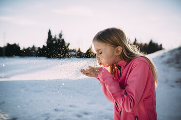 Side view of girl blowing confetti while standing on snow covered field against sky - CAVF59681