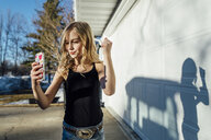Girl taking selfie while standing by house - CAVF59687