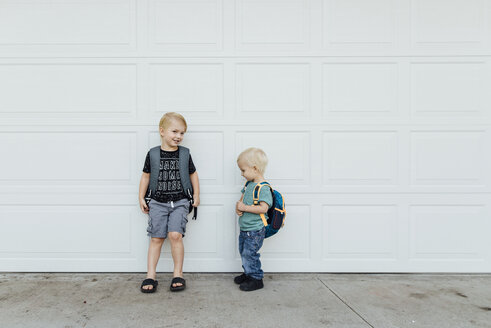 Brothers standing on footpath by wall - CAVF59696