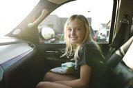 Portrait of smiling girl sitting in car - CAVF59699