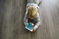 High angle view of boy using tablet computer while lying on floor at home - CAVF59753