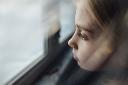 High angle view of thoughtful girl by window at home - CAVF59780