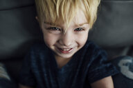 High angle portrait of smiling boy sitting on sofa at home - CAVF59786