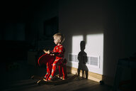 Baby boy looking away while sitting on rocking horse at home - CAVF59807
