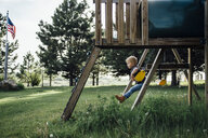 Side view of boy swinging at park - CAVF59822