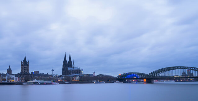Germany, Cologne, city view with Cologne Cathedral at blue hour - SKAF00069