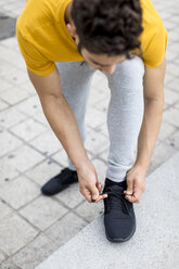 Young man during workout, tying shoes - MAUF01873