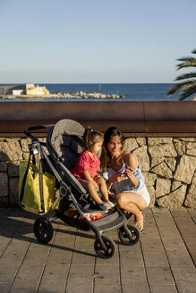 Mother kneeling next to daughter, sitting in pram, looking at smartphone - MAUF01897