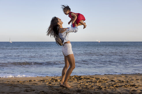 Mother and daughter having fun on the beach, pretending to fly - MAUF01909