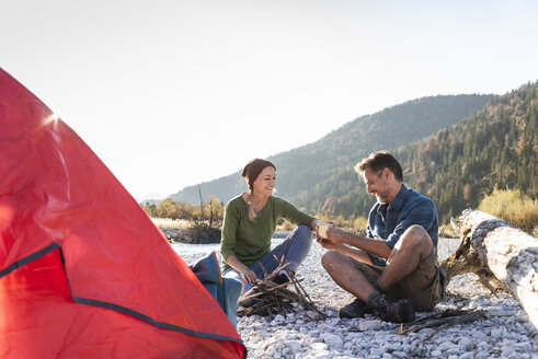 Mature couple camping at riverside in the evening light - UUF16270