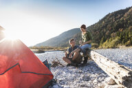 Mature couple camping at riverside in the evening light - UUF16273