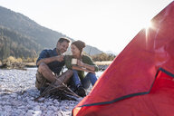 Mature couple camping at riverside in the evening light - UUF16276