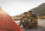 Mature couple camping at riverside in the evening light - UUF16279