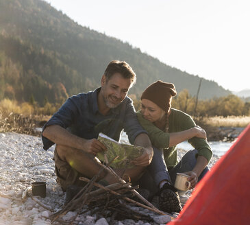 Mature couple camping at riverside, looking on map - UUF16282